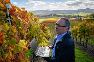 Greg Jones in the vineyard overlooking Abacela Winery, holding a laptop and downloading data